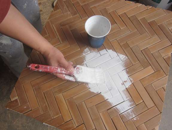 16. Flip table back upright; prime the herringbone top. Let dry, then brush on two coats