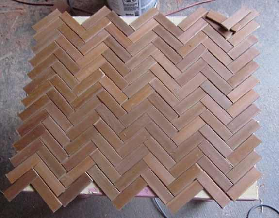 8. Once you have figured out the way you would like your herringbone pattern to go, clear the tabletop, find the center of your tabletop surface and lay the pieces starting from the center